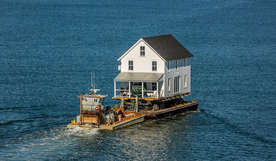 ADVANCE FOR SUNDAY DEC. 13 AND THEREAFTER - This Wednesday, Nov. 25, 2015 photo provided by At Altitude Gallery shows the historic store the Harvey Building being moved by barge from Oyster Va., to Cape Charles, Va. (Gordon Campbell/At Altitude Gallery via AP)