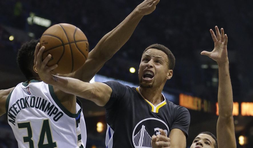 Golden State Warriors' Stephen Curry, middle, goes up for a layup between Milwaukee Bucks' Giannis Antetokounmpo, left, and Michael Carter-Williams, right, during the first half of an NBA basketball game Saturday, Dec. 12, 2015, in Milwaukee. (AP Photo/Aaron Gash)