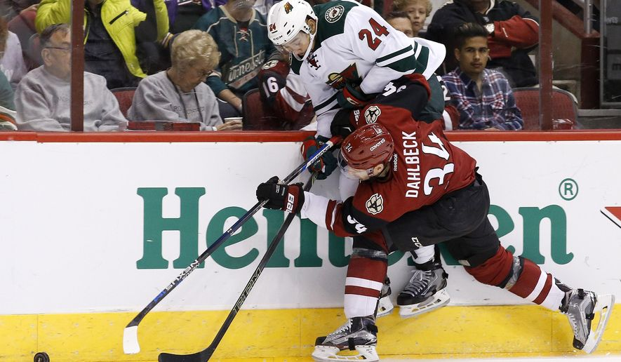 Arizona Coyotes' Klas Dahlbeck (34), of Sweden, shoves Minnesota Wild's Matt Dumba (24) into the boards during the first period of an NHL hockey game Friday, Dec. 11, 2015 in Glendale, Ariz. (AP Photo/Ross D. Franklin)