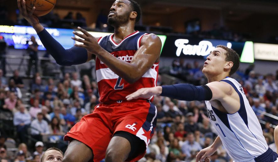 Washington Wizards guard John Wall (2) shoots in front of Dallas Mavericks forward Dwight Powell (7) during the first half an NBA basketball game, Saturday, Dec. 12, 2015, in Dallas. (AP Photo/Jim Cowsert)
