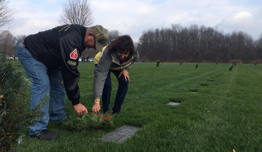 Volunteers place wreaths on the graves of veterans Saturday, Dec. 12, during a Wreaths Across America ceremony at Fort Custer National Cemetery in Augusta, Mich.  (Rex Hall Jr. /Kalamazoo Gazette-MLive Media Group via AP) LOCAL TELEVISION OUT; LOCAL RADIO OUT; MANDATORY CREDIT