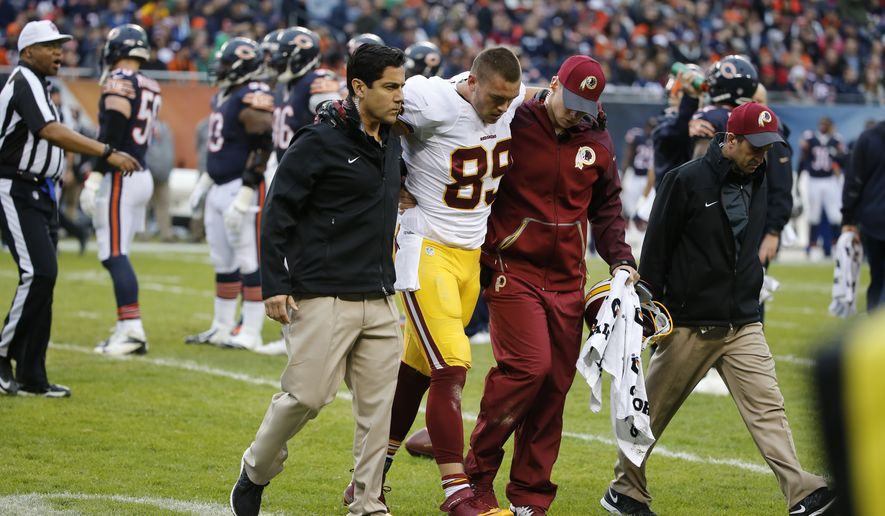 Washington Redskins tight end Derek Carrier (89) walks off the field with help from trainers during the first half of an NFL football game against the Chicago Bears, Sunday, Dec. 13, 2015, in Chicago. (AP Photo/Charles Rex Arbogast)