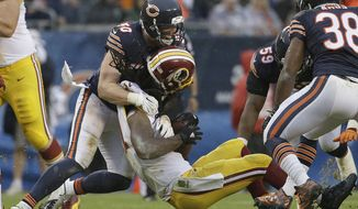Washington Redskins running back Matt Jones (31) loses his helmet as he is tackled by Chicago Bears inside linebacker Shea McClellin (50) during the second half of an NFL football game, Sunday, Dec. 13, 2015, in Chicago. (AP Photo/Nam Y. Huh)
