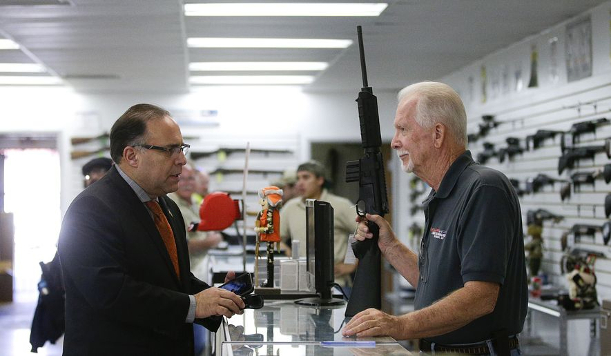 Sales associate Mike Conway (right) shows Paul Angulo a semiautomatic rifle at Bullseye Sport gun shop in Riverside, Calif., on Dec. 9, 2015. (Associated Press) **FILE**