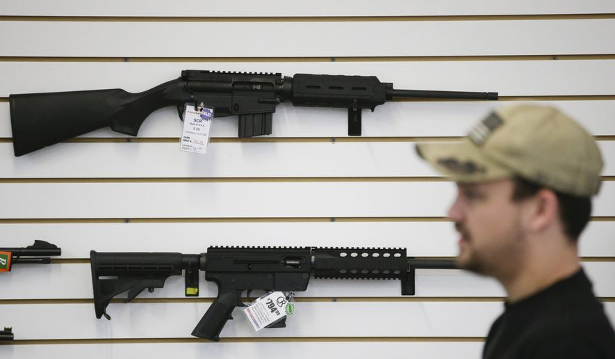A sales associate walks past semiautomatic rifles at Bullseye Sport gun shop in Riverside, Calif., in this Dec. 9, 2015, file photo. (AP Photo/Jae C. Hong)
