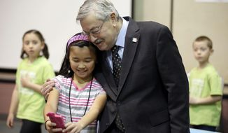 In this Monday, Dec. 7, 2015, photo, Iowa Gov. Terry Branstad poses for a photo with sixth-grader Elaine Wang before speaking at a proclamation signing at Jordan Creek Elementary School, in West Des Moines, Iowa. On Dec. 14, the six-term Republican will mark his 7,642nd day of service as governor, making him the longest-serving governor in American history. (AP Photo/Charlie Neibergall)