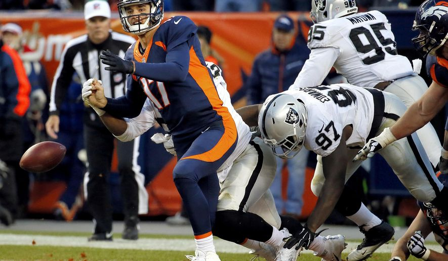 Denver Broncos quarterback Brock Osweiler (17) has the ball stripped by Oakland Raiders defensive end Khalil Mack, rear, as defensive end Mario Jr. Edwards (97) defends in the end zone for a safety during the second half of an NFL football game, Sunday, Dec. 13, 2015, in Denver. (AP Photo/Jack Dempsey)