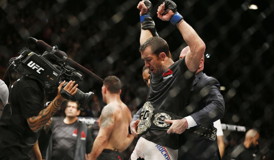 Luke Rockhold, right, reacts after defeating Chris Weidman, left, in a middleweight  championship mixed martial arts bout at UFC 194, Saturday, Dec. 12, 2015, in Las Vegas. (AP Photo/John Locher)