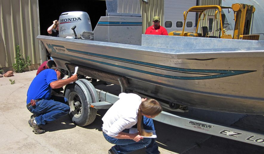 FILE - In this 2011 file photo provided by the Wyoming Game and Fish Department, unidentified students practice inspecting a boat for quagga mussels and other aquatic invasive species during a training course in Lander, Wyo. Wyoming has succeeded in preventing invasive zebra and quagga mussels from entering the state's streams and reservoirs for another year. The Wyoming Game and Fish Department said its annual boat inspection program checked 45,967 boats entering the state in 2015, finding three contaminated boats.(Wes Gordon/Wyoming Game and Fish Department via AP, File)