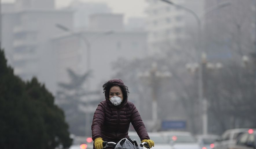 A woman wears a mask as she rides across a road on a polluted day in Beijing, Sunday, Dec. 13, 2015. China's push for a global climate pact is partly because of its own increasingly pressing need to solve serious environmental problems, observers said Sunday. (AP Photo/Andy Wong)
