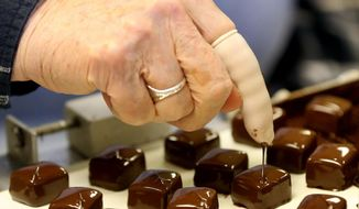 A squiggle is applied to each chocolate-covered caramel Monday, Sept. 28, 2015, at Our Lady of the Mississippi Abbey in Dubuque, Iowa. (Jessica Reilly/Telegraph Herald via AP)