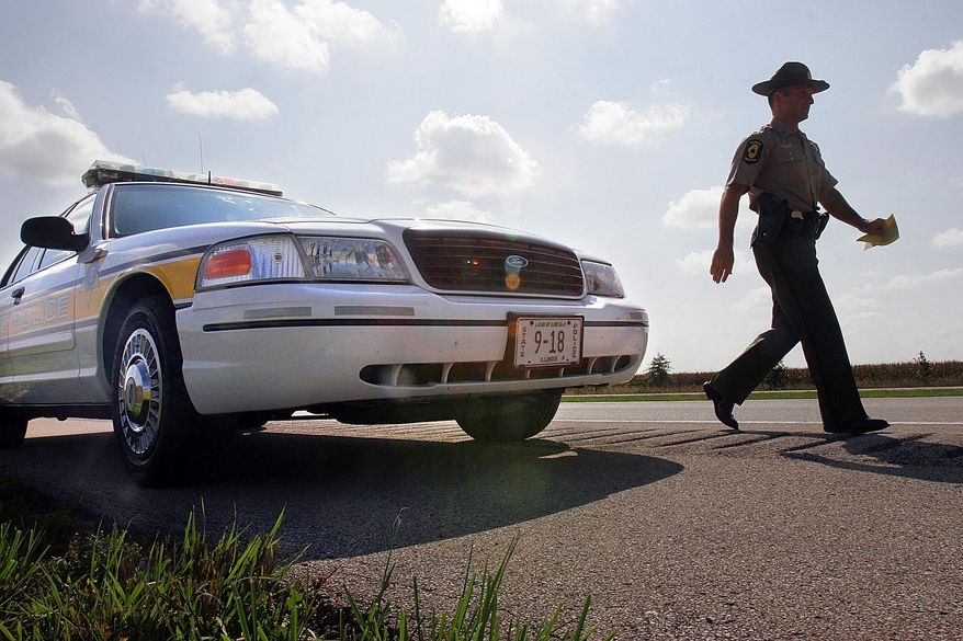 In this Sept. 15, 2006, file photo, Illinois State Police Officer Sgt. Mike Vorreyer walks from his patrol car to issue a ticket for speeding to a driver on Interstate 72 near Jacksonville, Ill. (AP Photo/Seth Perlman, File)