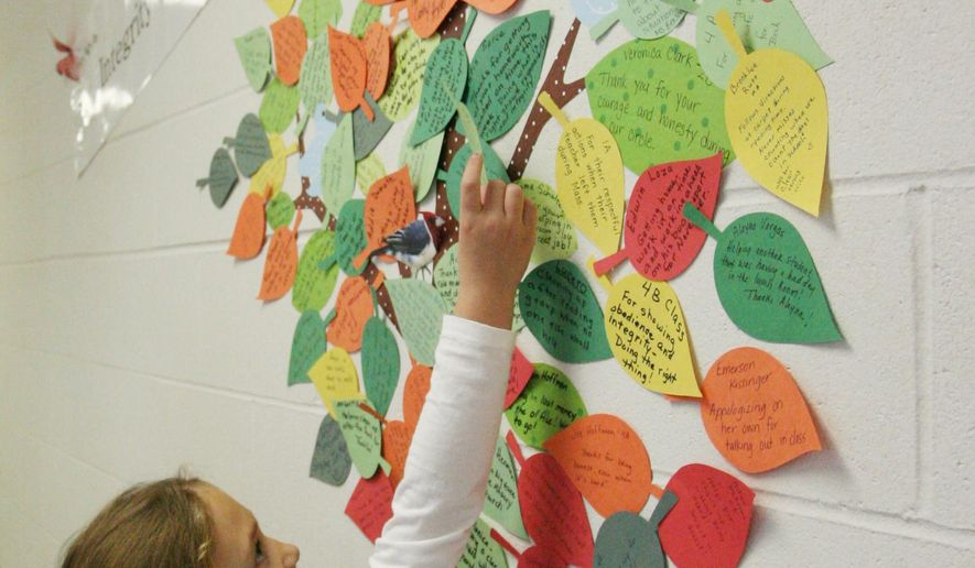 ADVANCE FOR THE WEEKEND OF DEC. 12-13 AND THEREAFTER - In a Dec. 1, 2015 photo, St. Michael's Elementary School first-grader Lydia Pearce places her leaf on the Virtue Tree at the school in Hastings, Neb.Students caught doing good deeds are given a leaf written with the deed on it to place on the tree. (Amy Roh/Hastings Tribune via AP)