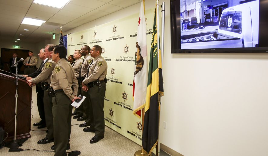 An video released by Los Angeles County Sheriff is shown on a television screen during a news conference about Saturday's fatal shooting of a man in Lynwood, Sunday, Dec. 13, 2015, in Los Angeles. A black man who was fatally shot by Los Angeles deputies kept holding a gun as he lay dying on the ground, authorities said Sunday in response to questions about why they continued to fire on the man after he fell to the pavement.  (AP Photo/Ringo H.W. Chiu)