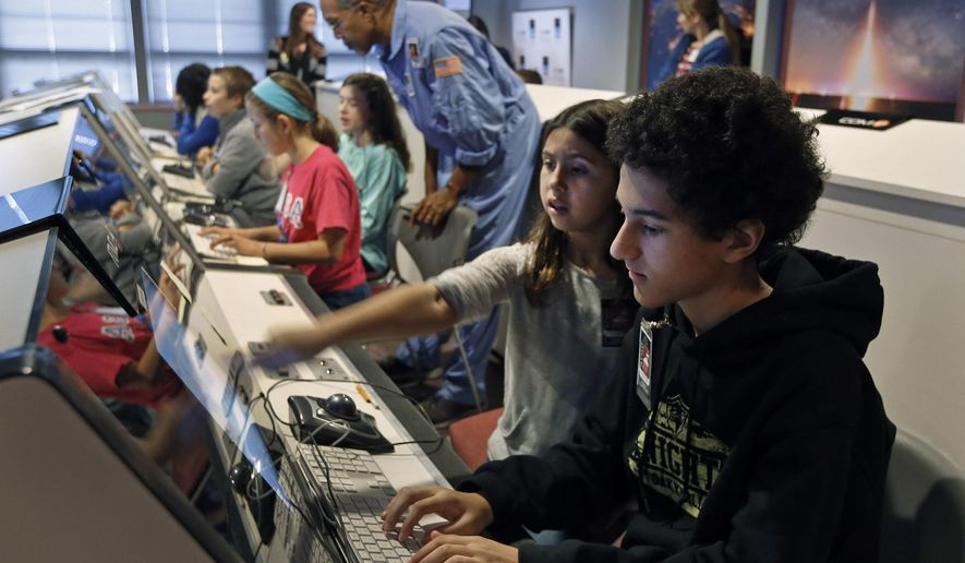 ADVANCE FOR MONDAY, DEC. 14 AND THEREAFTER - In a Nov. 17, 2015 photo, while Brent Michael Peterson, 11, right, of Oak Knoll Middle School and Kate Faulkner, 11, of Stonewall Jackson Middle School watch monitors in the mission control room at the Math Science Innovation Center, educator Jerome Randolph, standing, center, works with other students. Mission control stays in touch with other students who are manning the Challenger Space Station.   (P. Kevin Morley/Richmond Times-Dispatch via AP)