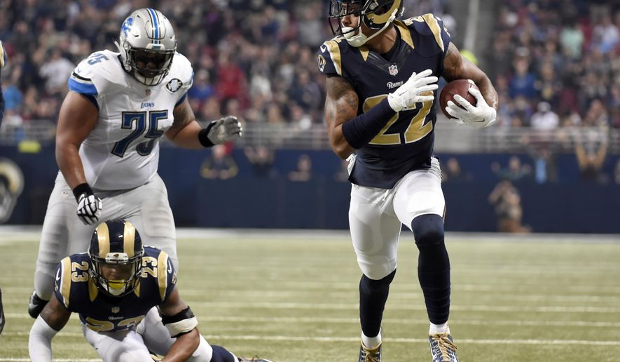 St. Louis Rams cornerback Trumaine Johnson, right, runs an interception back 58-yards for a touchdown as teammate Rodney McLeod (23) and Detroit Lions guard Larry Warford (75) watch during the second quarter of an NFL football game Sunday, Dec. 13, 2015, in St. Louis. (AP Photo/L.G. Patterson)