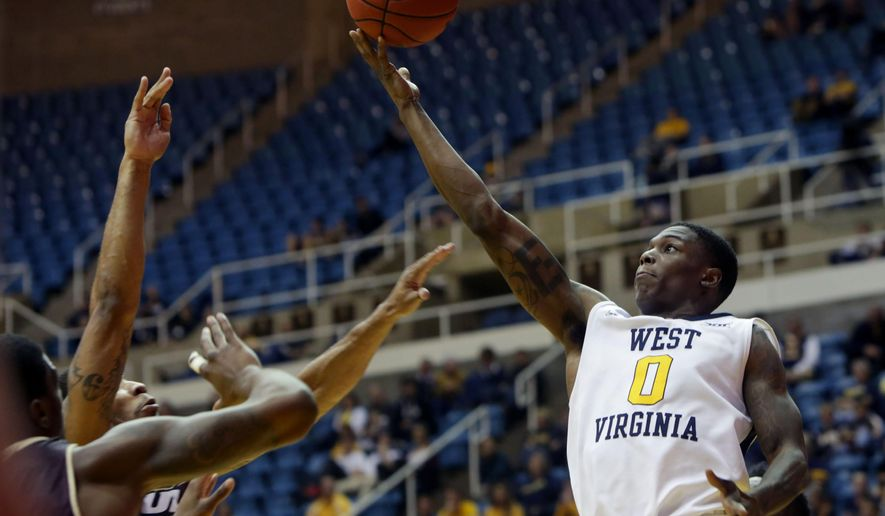 West Virginia guard Teyvon Myers (0) drives to the basket while being defended by Louisiana-Monroe guard Marcus Washington (3) during the second half of an NCAA college basketball game, Sunday, Dec, 13, 2015, in Morgantown, W.Va. West Virginia defeated Louisiana-Monroe 100-58. (AP Photo/Raymond Thompson)