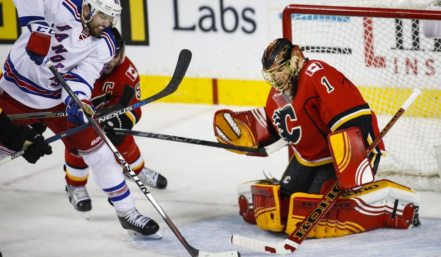 New York Rangers' Rick Nash, left, battles for the puck in front of Calgary Flames' goalie Jonas Hiller, of Switzerland, during third period NHL hockey action, in Calgary, on Saturday, Dec. 12, 2015. (Jeff McIntosh/The Canadian Press via AP)