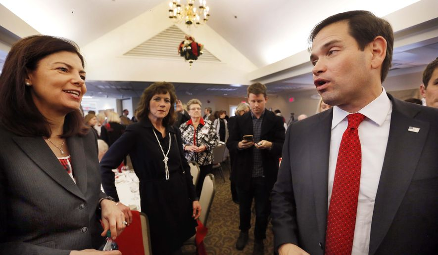 In this photo taken Friday, Dec. 4, 2015, U.S. Sen. Kelly Ayotte, R-N.H., left crosses paths with Republican presidential candidate Sen. Marco Rubio, R-Fla., during a stop at the Seacoast Republican Women's Holiday Luncheon in Greenland, N.H. Ayotte, who is seeking re-election in November, has made some votes that upset members of her own Republican party. (AP Photo/Jim Cole)