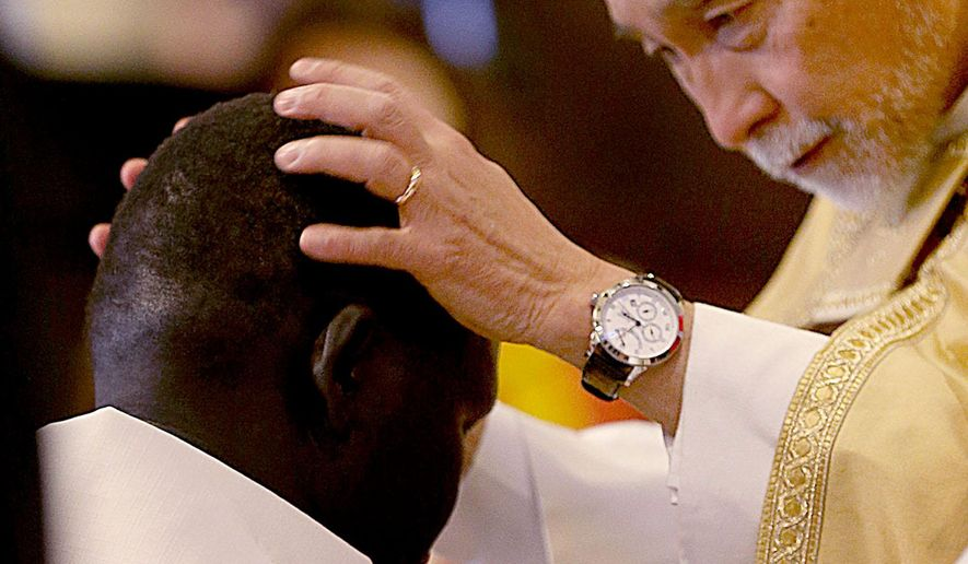 FILE - In this Saturday, Dec. 5, 2015 file photo, Rev. Scott Hayashi ordains Gabriel Atem as a deacon within the Episcopal Church at the Cathedral Church of Saint Mark in Salt Lake City. Atem was one of thousands of Sudanese children choosing to flee instead of being forced to fight in a civil war. (Laura Seitz/The Deseret News via AP, File)  SALT LAKE TRIBUNE OUT; MAGS OUT; MANDATORY CREDIT; TV OUT)