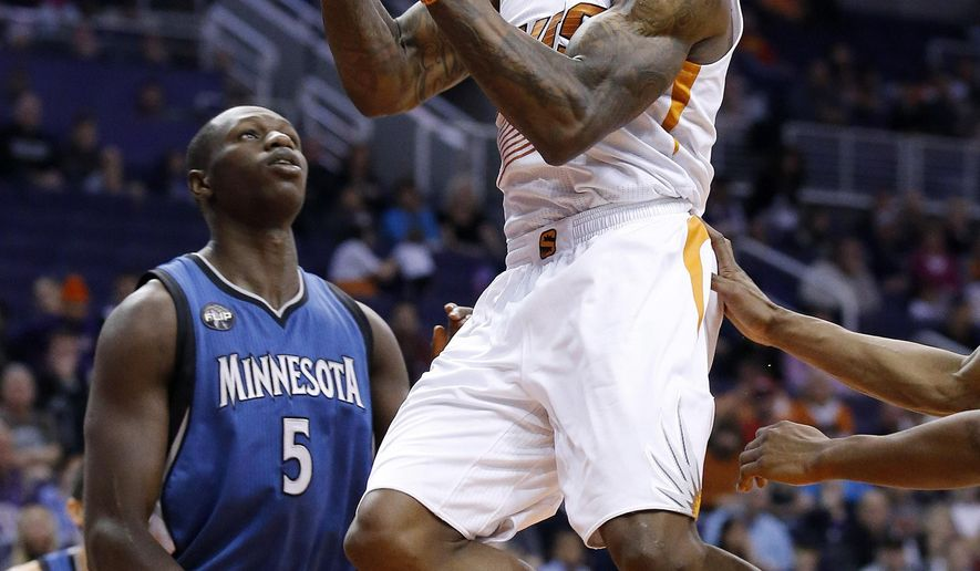 Phoenix Suns' Eric Bledsoe, right, drives past Minnesota Timberwolves' Gorgui Dieng (5), of Senegal, during the first half of an NBA basketball game Sunday, Dec. 13, 2015, in Phoenix. (AP Photo/Ross D. Franklin)