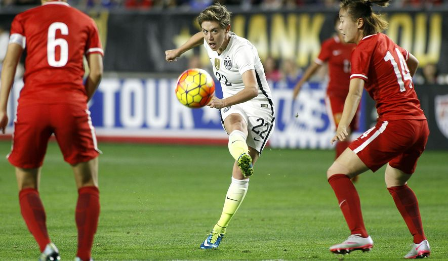 United States' Meghan Klingenberg (22) kicks a shot toward the goal between China's Li Dongna (6) and Zhao Rong during the first half of an international friendly soccer match, Sunday, Dec. 13, 2015, in Phoenix. (AP Photo/Ralph Freso)