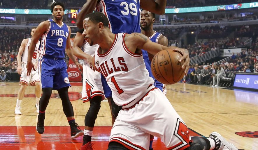 Chicago Bulls guard Derrick Rose (1) drives the baseline past the defense of Philadelphia 76ers forward Jerami Grant (39) as Jahlil Okafor (8) watches, during the first half of an NBA basketball game Monday, Dec. 14, 2015, in Chicago. (AP Photo/Charles Rex Arbogast)
