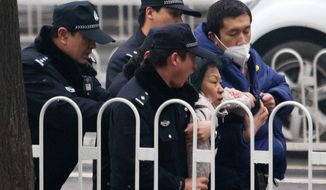 Police officers take away a supporter of rights lawyer Pu Zhiqiang near the Beijing Second Intermediate People's Court during his trial in Beijing, Monday, Dec. 14, 2015. Pu went on trial Monday on charges of provoking trouble with commentaries on social media that were critical of the ruling Communist Party. (AP Photo/Andy Wong)