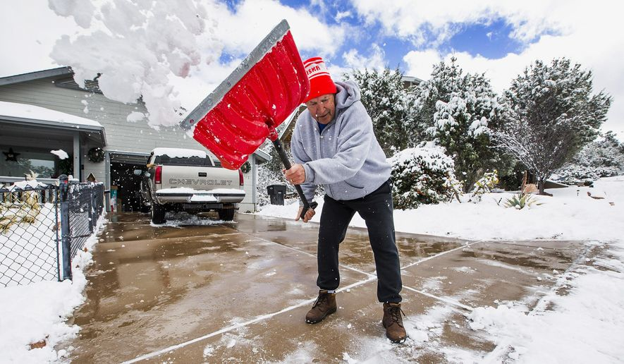 David Rutter, a full-time resident of Payson, shovels his driveway after snow fell, covering the area with a few inches in Payson, Ariz., Monday, Dec. 14, 2015. A storm that dumped snow on northern Arizona left traffic crawling along powder-packed highways and canceled schools Monday, with blistering cold weather expected to follow in its wake. (Tom Tingle/The Arizona Republic via AP)