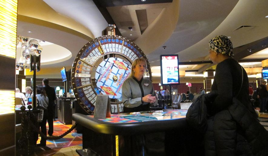 This April 17, 2015 photo shows a customer playing a cash wheel game at the Tropicana casino in Atlantic City, N.J. Figures released on Monday, Dec. 14, 2015 show the city's eight casinos saw their winnings increase by less than 1 percent in November, but it would have been a down month had it not been for a big boost from Internet gambling. (AP Photo/Wayne Parry)
