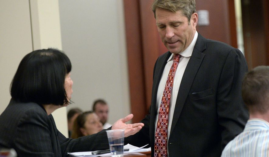 State prosecutor Chou Chou Collins, left, huddles with defense lawyer Scott Williams prior to a status hearing for former Utah Attorney General John Swallow in Salt Lake City on Monday, Dec. 14, 2015. A judge delayed an April trial date in the pay-to-play case against Swallow on Monday, after his lawyer said the defense needs more time to go through the large amount of evidence. (Al Hartmann/The Salt Lake Tribune via AP, Pool)