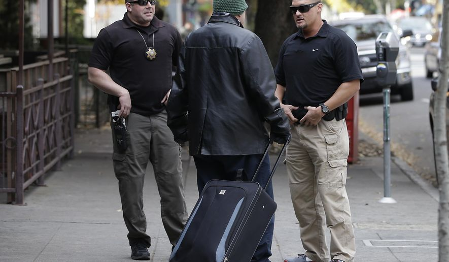 In this photo taken Tuesday, Dec. 1, 2015, parole agents Andrew Correa, left, and Clint Cooley, right, talk with a sex-offender parolee they located by tracking the global positioning device he wears, in Sacramento, Calif.  Parole agents use a global positioning devices to locate parolees to make unannounced stops.  State corrections officials recently completed a review how many sex offenders must comply with voter-approved residency restrictions based on a state supreme court decision.  The corrections department announced a dramatic reduction in the number of offenders barred from living near schools and parks.(AP Photo/Rich Pedroncelli)