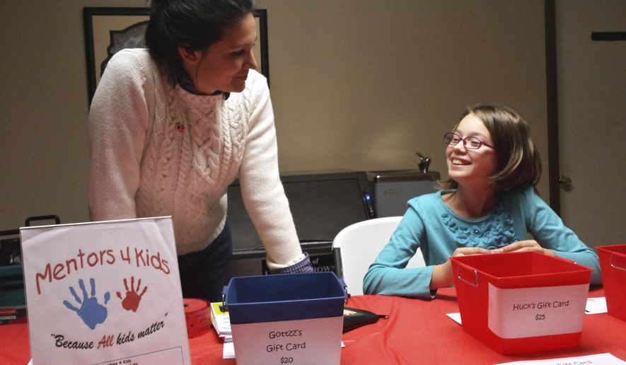 In this Nov. 14, 2015 photo, Maggie Gonzalez, left, and 12-year-old Hope Taylor spend time together on a variety of projects, including raising money for the Harrisburg, Ill.-based Mentors 4 Kids program during a fundraiser for the mentoring program in Carmi, Ill. The program brought the two together as a match. Gonzalez is also a case manager for the program that serves six counties. (Nick Mariano/The Southern via AP)