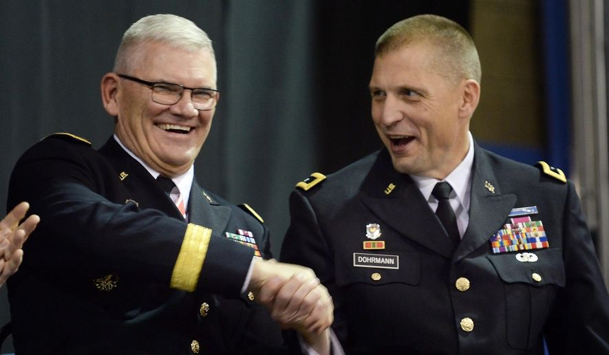North Dakota National Guard retiring Adjutant Gen. David Sprynczynatyk, left, shares a laugh with incoming Adjutant Gen. Alan Dohrmann during the change of command ceremony in Bismarck, Sunday, Dec. 13, 2015. Sprynczynatyk is retiring after 43 years of military service. He has been the Adjutant General of North Dakota since 2006. (Will Kincaid/The Bismarck Tribune via AP) MANDATORY CREDIT