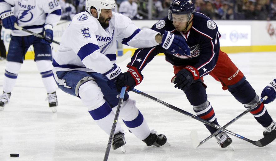 Tampa Bay Lightning's Jason Garrison, left, works for the puck against Columbus Blue Jackets' Alexander Wennberg, of Sweden, during the second period of an NHL hockey game in Columbus, Ohio, Monday, Dec. 14, 2015. (AP Photo/Paul Vernon)