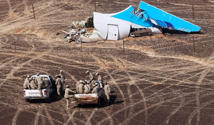 """FILE - In this Sunday, Nov. 1, 2015 photo provided by Russian Emergency Situations Ministry, Egyptian Military on cars approach a plane's tail at the wreckage of a passenger jet bound for St. Petersburg in Russia that crashed in Hassana, Egypt. Egypt's chief investigator says a preliminary investigation into the October crash of a Russian passenger plane in Sinai has found no indication yet of any """"illegal or terrorist act."""" (Maxim Grigoriev/Russian Ministry for Emergency Situations via AP, File)"""