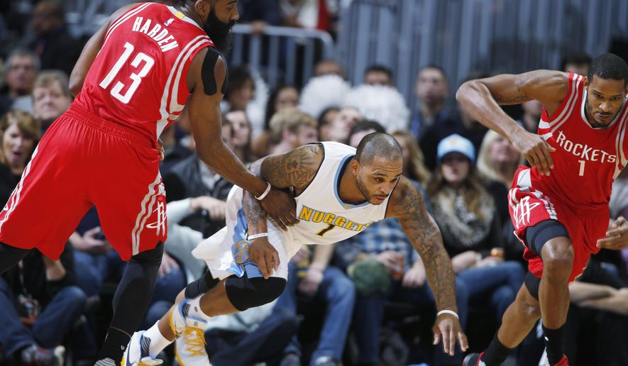 Denver Nuggets guard Jameer Nelson, center, pursues a loose ball with Houston Rockets forward Trevor Ariza, right, and  guard James Harden in the first half of an NBA basketball game Monday, Dec.14, 2015, in Denver. (AP Photo/David Zalubowski)