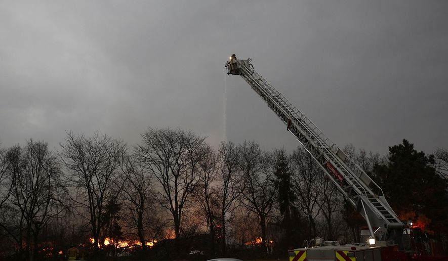 Fire fighters continue to battle a warehouse blaze on the West Side, Monday morning, Dec. 14, 2015 in Columbus, Ohio. No injuries were reported in the blaze that lit the skies for miles along I-70 in Columbus early Monday and led two schools to cancel classes.  (Eamon Queeney/The Columbus Dispatch via AP)