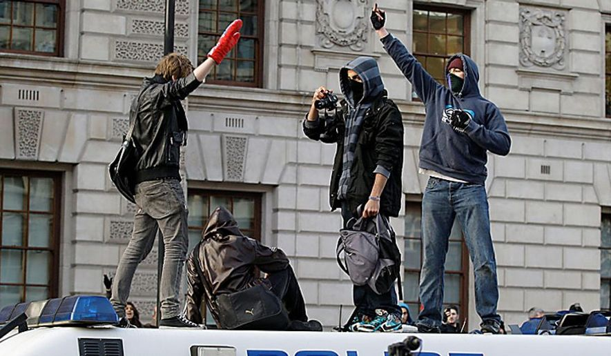 Protesters gesture on top of a stranded police van as thousands of students protest against increased tuition fees at Whitehall in London, Wednesday, Nov. 24, 2010. (AP Photo/Sang Tan)