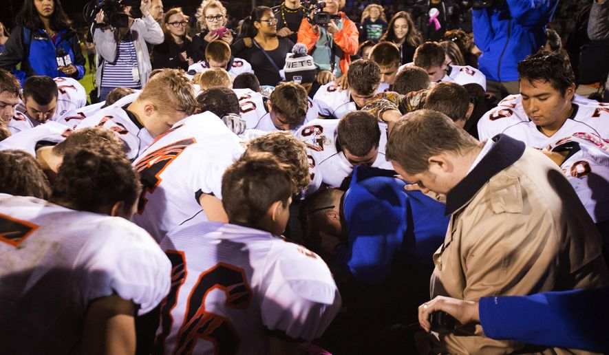 In this Oct. 16, 2015, photo, Bremerton High School assistant football coach Joe Kennedy, center in blue, kneels and prays after his team lost to Centralia in Bremerton, Wash. Kennedy, who was suspended for praying at midfield after games, has filed a discrimination complaint on Tuesday, Dec. 15, 2015 with the U.S. Equal Employment Opportunity Commission according to The Liberty Institute, a Texas-based law firm representing the coach. (Lindsey Wasso(/The Seattle Times via AP, File) SEATTLE OUT; USA TODAY OUT; MAGS OUT; TELEVISION OUT; NO SALES; MANDATORY CREDIT TO BOTH THE SEATTLE TIMES AND THE PHOTOGRAPHER
