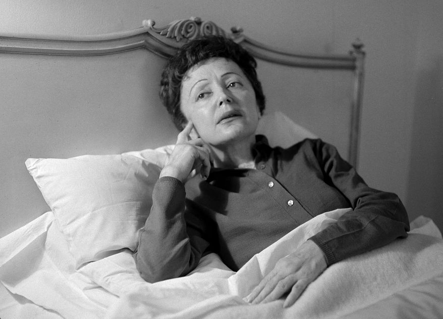 """FILE - In this Feb. 20, 1959 file photo, French songstress Edith Piaf props up in bed after an undisclosed illness resulted in the cancellation of scheduled performances at the Waldorf-Astoria Hotel in New York. Piaf, famous for her hit """"La Vie En Rose,"""" would have turned 100 on Dec. 19, 2015. At only 4 feet 8 inches, her voice was strong and distinctive, a trembling alto wail that became the voice of the Paris working class. Piaf died on Oct. 10, 1963, from exhaustion and liver disease at the age of 47. (AP Photo/Matty Zimmerman, File)"""