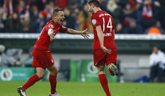 Bayern's Xabi Alonso, right, celebrates with teammate Rafinha after scoring his side's opening goal during the German soccer cup (DFB Pokal) match between FC Bayern Munich and SV Darmstadt 98 at the Allianz Arena stadium in Munich, Germany, Tuesday, Dec. 15, 2015. (AP Photo/Matthias Schrader)