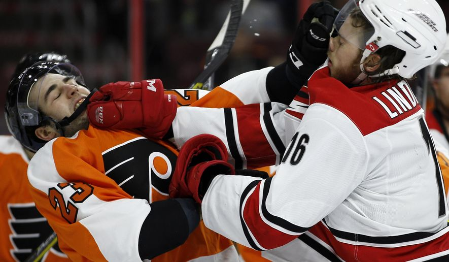 Philadelphia Flyers' Brandon Manning, left, and Carolina Hurricanes' Elias Lindholm scuffle in front of the net during the third period of an NHL hockey game Tuesday, Dec. 15, 2015, in Philadelphia. Philadelphia won 4-3 in overtime. (AP Photo/Matt Slocum)