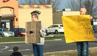 A photograph of a man holding a sign calling out a couple of panhandlers who allegedly turned down his job offer has gone viral. (Facebook/@Michael Wooldridge)