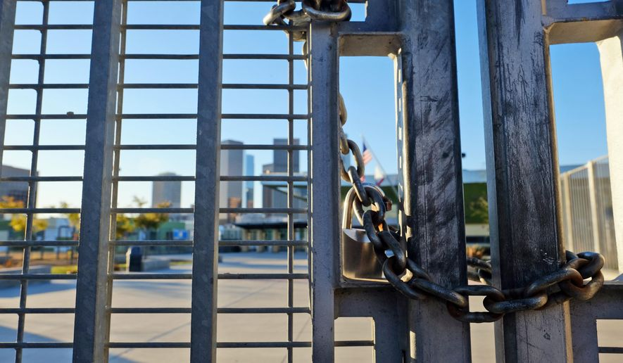 A lock holds the gate shut at Edward Roybal High School in Los Angeles, on Tuesday morning, Dec. 15, 2015. All schools in the vast Los Angeles Unified School District, the nation's second largest, have been ordered closed due to an electronic threat Tuesday. (AP Photo/Richard Vogel)