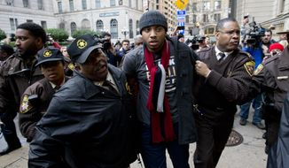 A demonstrator is detained outside of the courthouse in Baltimore on Wednesday after a mistrial of Officer William Porter, one of six Baltimore city police officers charged in connection to the death of Freddie Gray. (Associated Press)