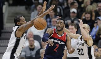 Washington Wizards guard John Wall (2) is pressured by San Antonio Spurs forward Kawhi Leonard, left, and guard Manu Ginobili (20) during the second half of an NBA basketball game, Wednesday, Dec. 16, 2015, in San Antonio. San Antonio won 114-95. (AP Photo/Eric Gay)