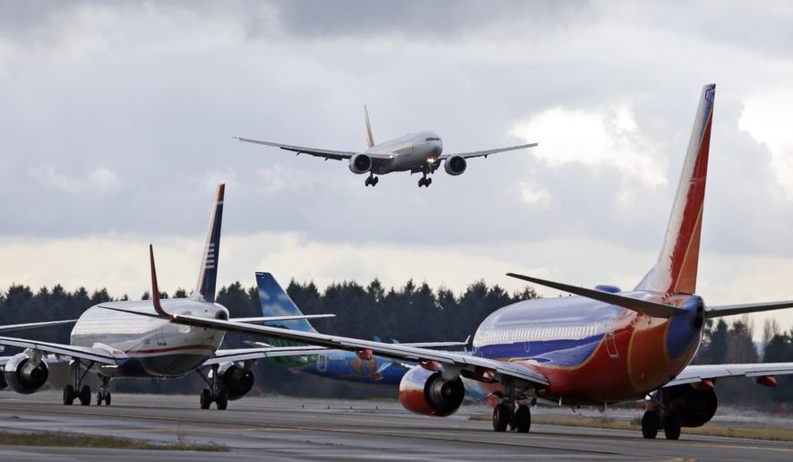 One passenger jet comes in for a landing and in view of a line of planes waiting to takeoff, Wednesday, Dec. 16, 2015, at Seattle-Tacoma International Airport, in SeaTac, Wash. (AP Photo/Elaine Thompson) ** FILE **