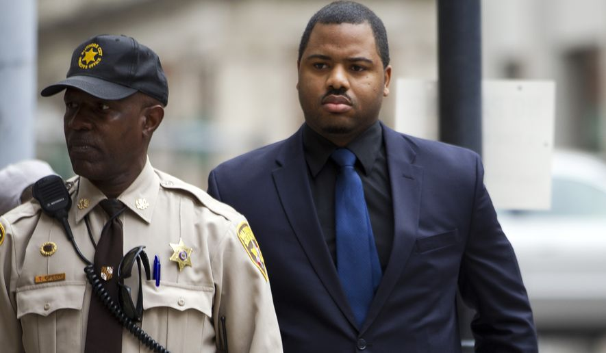 Officer William Porter, right, one of six Baltimore city police officers charged in connection to the death of Freddie Gray, arrives at a courthouse as jury deliberations continue in his trial, Wednesday, Dec. 16, 2015, in Baltimore Md. (Associated Press) **FILE**