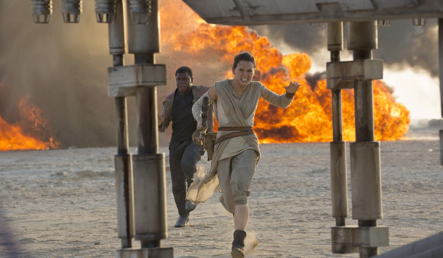 "This photo provided by Disney/Lucasfilm shows Daisy Ridley, right, as Rey, and John Boyega as Finn, in a scene from the film, ""Star Wars: The Force Awakens,"" directed by J.J. Abrams. Early screenings of the film begin Thursday night, Dec. 17, 2015. (David James/Disney/Lucasfilm via AP)"